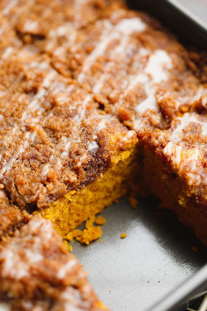 close up on a cut slice of brown pumpkin coffee cake in a metal baking tin.