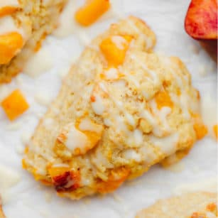 close up on a baked peach scone with a white glaze on top