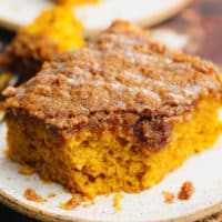 close up on a square slice of orange pumpkin coffee cake on a white plate.