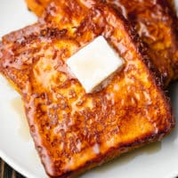 close up on a slice of vegan pumpkin french toast on a white plate topped with a square of butter.