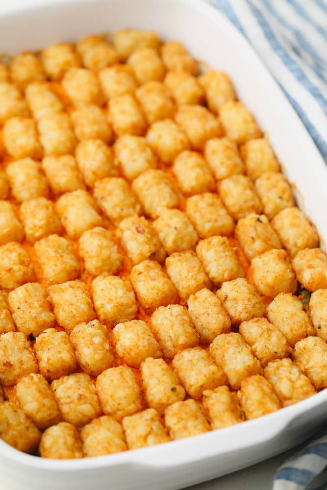 rows of baked tater tots in a white casserole dish.