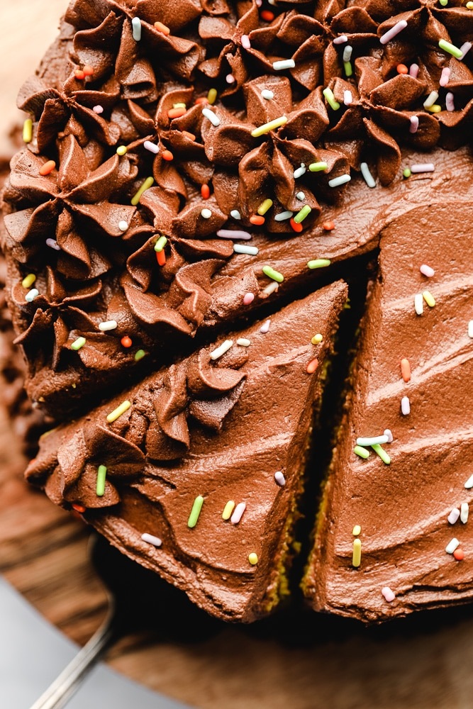 Removing a slice of chocolate-frosted cake.