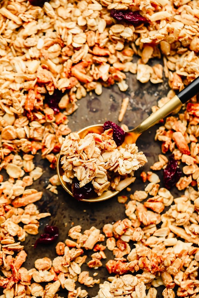 a spoonful of granola surrounded by more granola on a baking sheet.