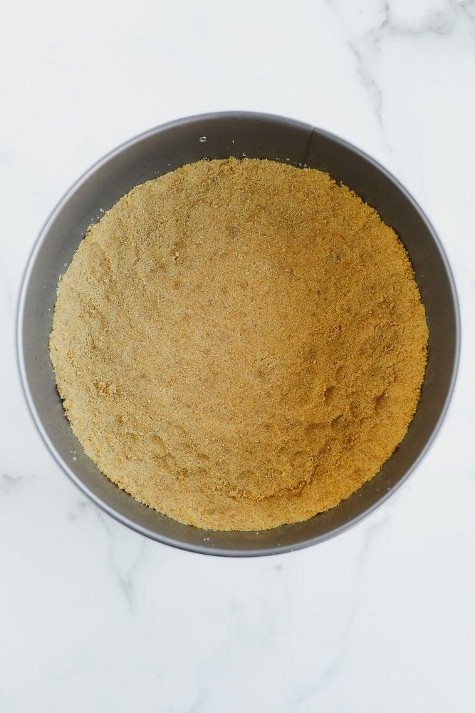 golden brown graham cracker crust on the bottom of a round metal pan.