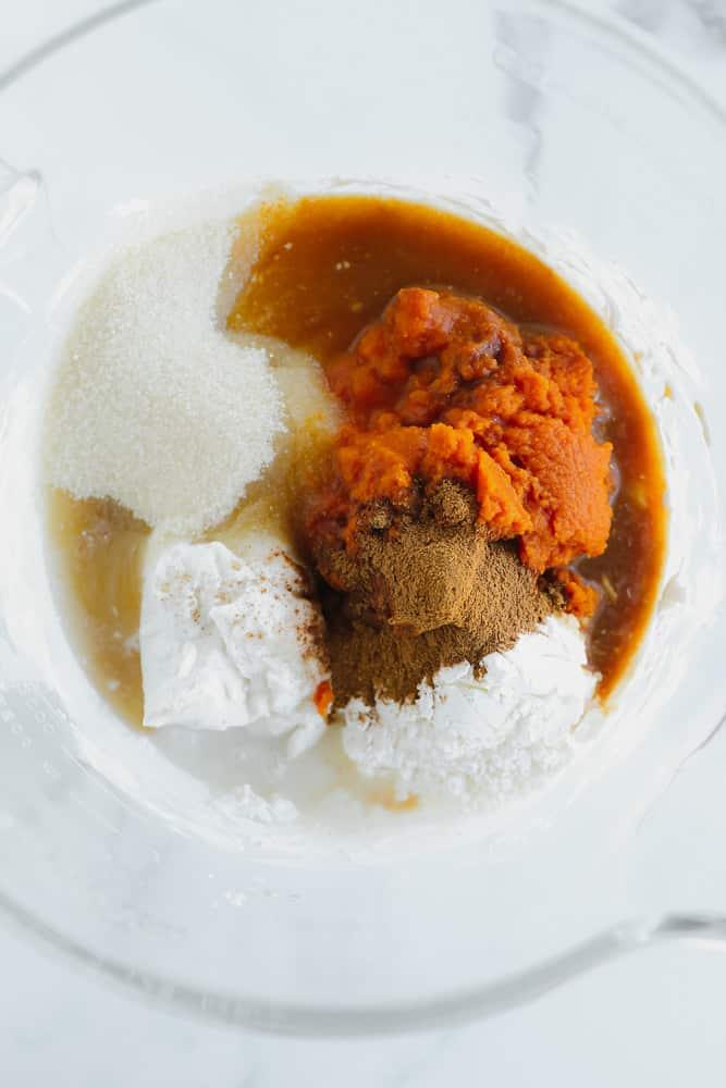 pumpkin puree, sugar, coconut cream, liquid, and spices in a pile in a glass bowl.