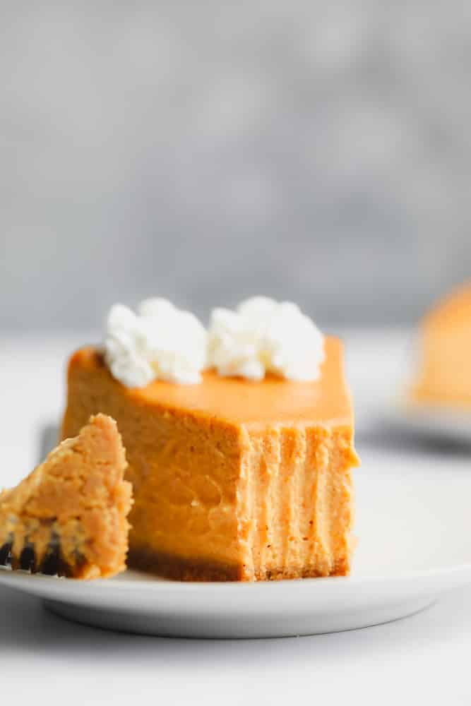 a slice of pumpkin cheesecake topped with whipped cream and a bite removed.