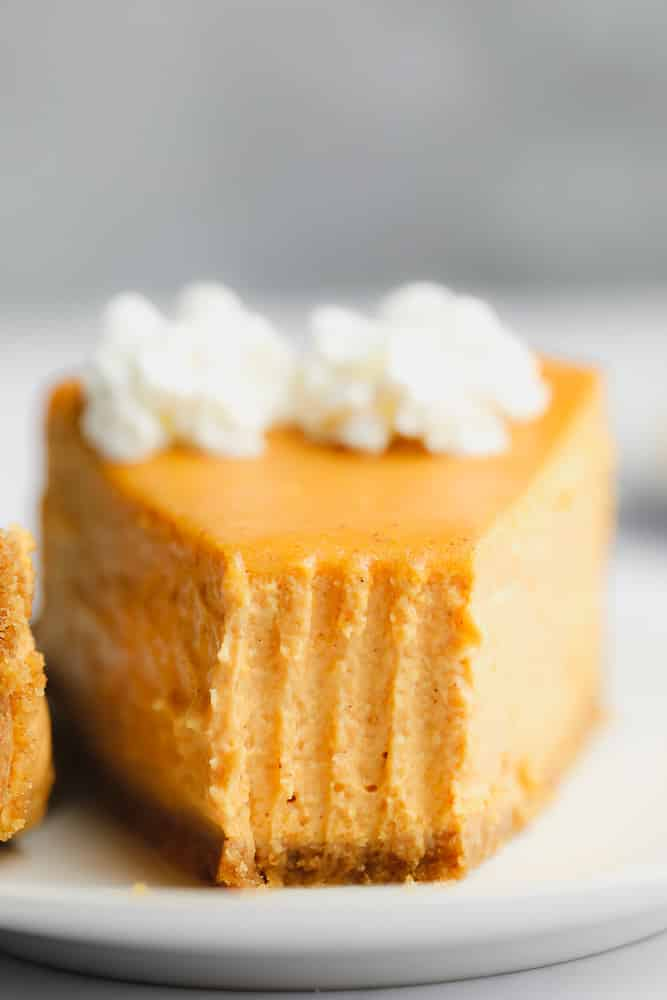 close up on a slice of pumpkin cheesecake with a bite missing.