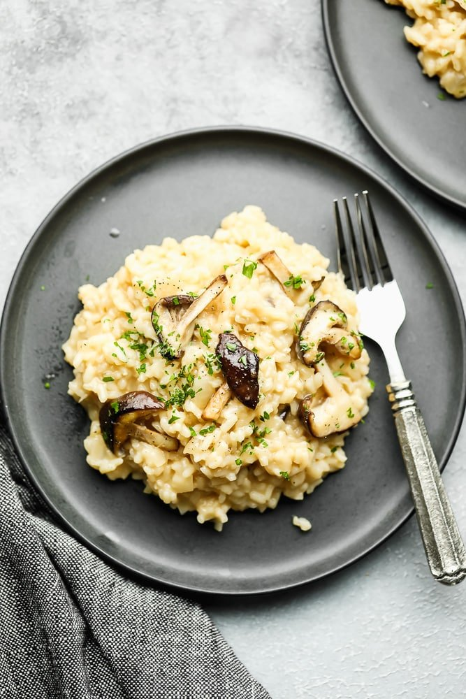 a scoop of creamy risotto topped with cooked mushrooms on a grey plate with a fork.