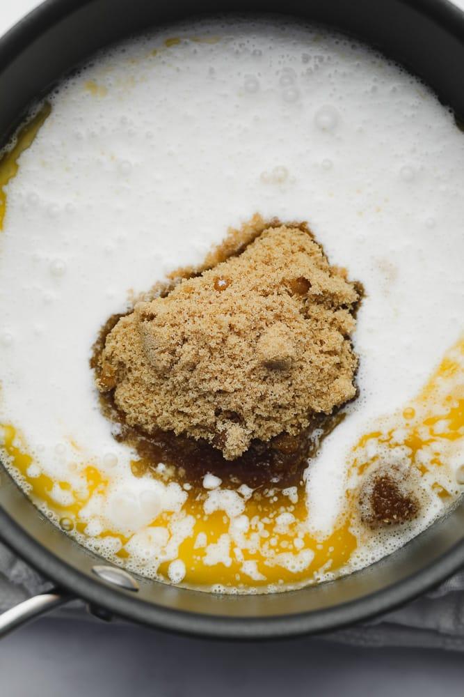 milk, butter, and brown sugar in a black saucepan.