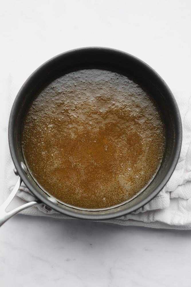 a thin golden brown sauce in a black saucepan.