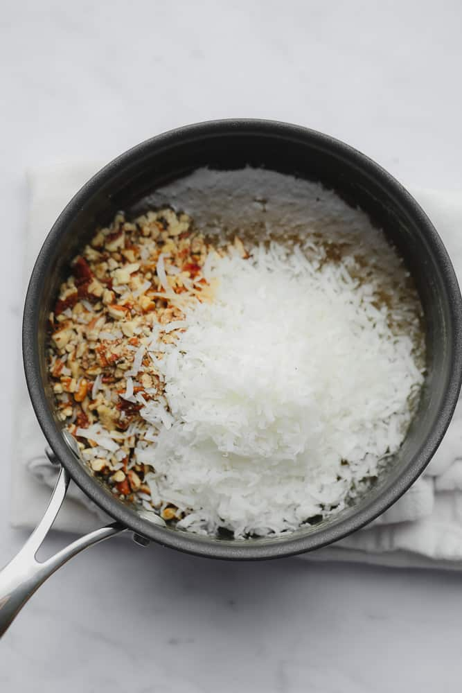 coconut shreds and chopped pecans in top of a caramel sauce in a black saucepan.