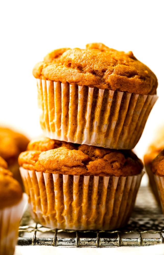 stack of two muffins that are orange, white background