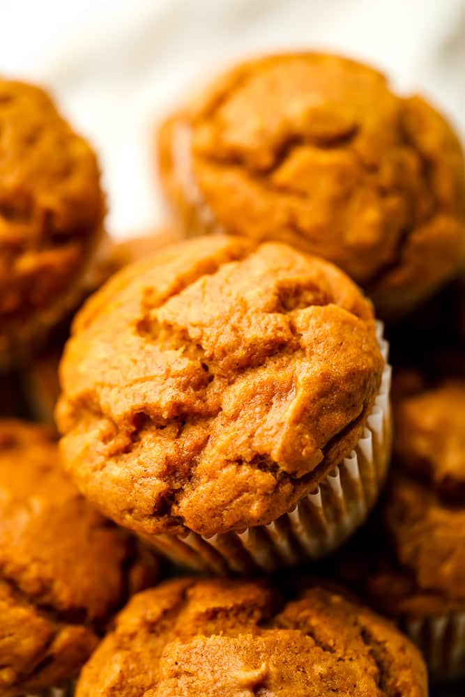 lots of vegan pumpkin muffins on top of each other, white background