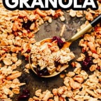pinterest image of a spoonful of granola surrounded by more granola on a baking sheet.