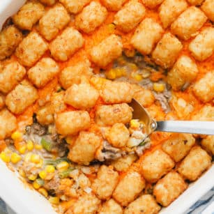 metal spoon scooping some baked tater tot casserole out of a white casserole dish.