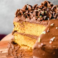 yellow cake with chocolate frosting with slices missing on a wood board.