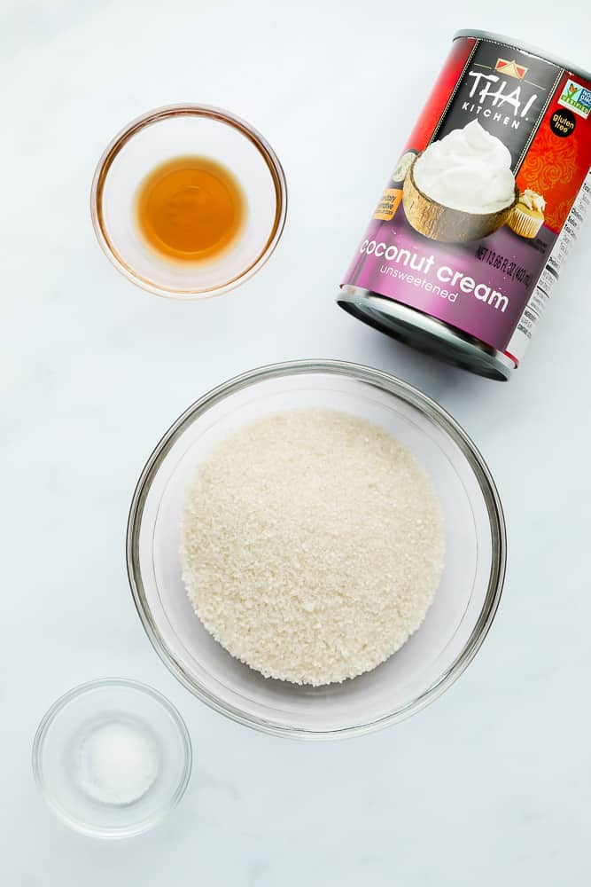 a can of coconut cream next to small glass bowls filled with sugar, vanilla, and salt.