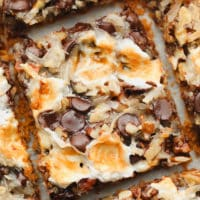 close up on a cut cookie bar with toasted marshmallows, coconut, and chocolate on top.