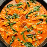wilted spinach, cubed butternut squash, and chickpeas in an orange liquid in a black skillet.